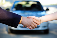Shaking hands in front of car